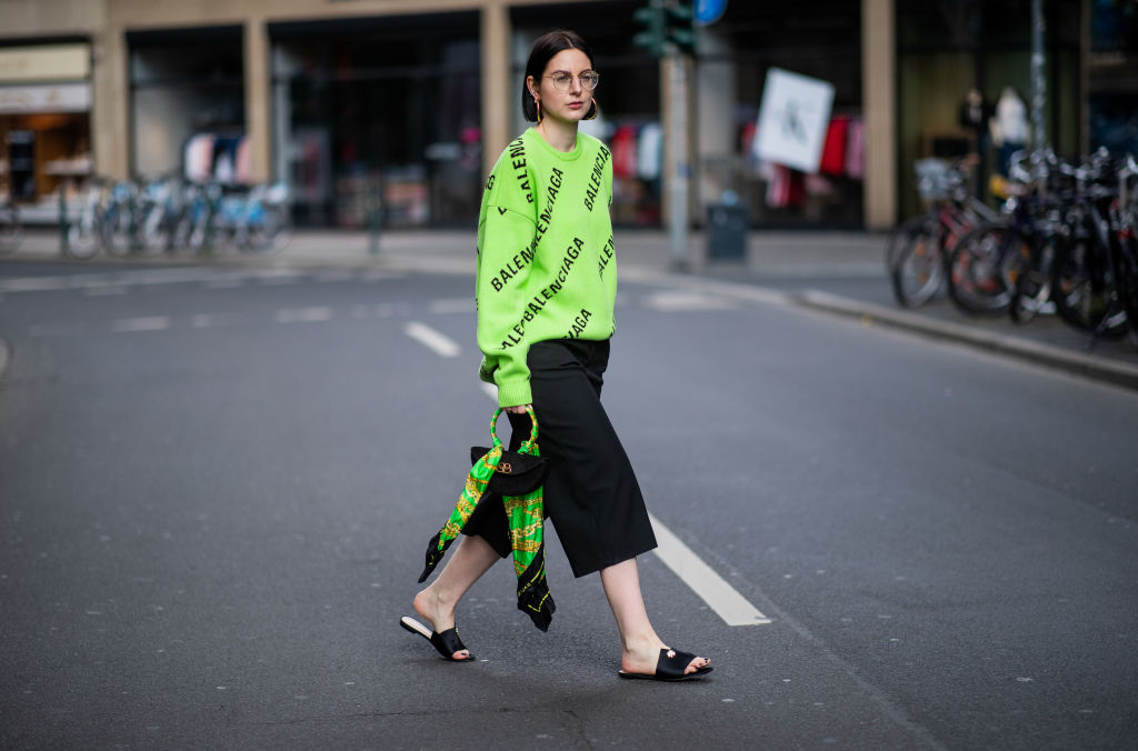 DUESSELDORF, GERMANY - MAY 05: Maria Barteczko is seen wearing neon green logo sweater Balenciaga, black culotte trousers Zara, black slipper March & Muse, black operat clutch bag Balenciaga, hoops Galleria Armadoro, round glasses Ray Ban on May 05, 2019 in Duesseldorf, Germany. (Photo by Christian Vierig/Getty Images)
