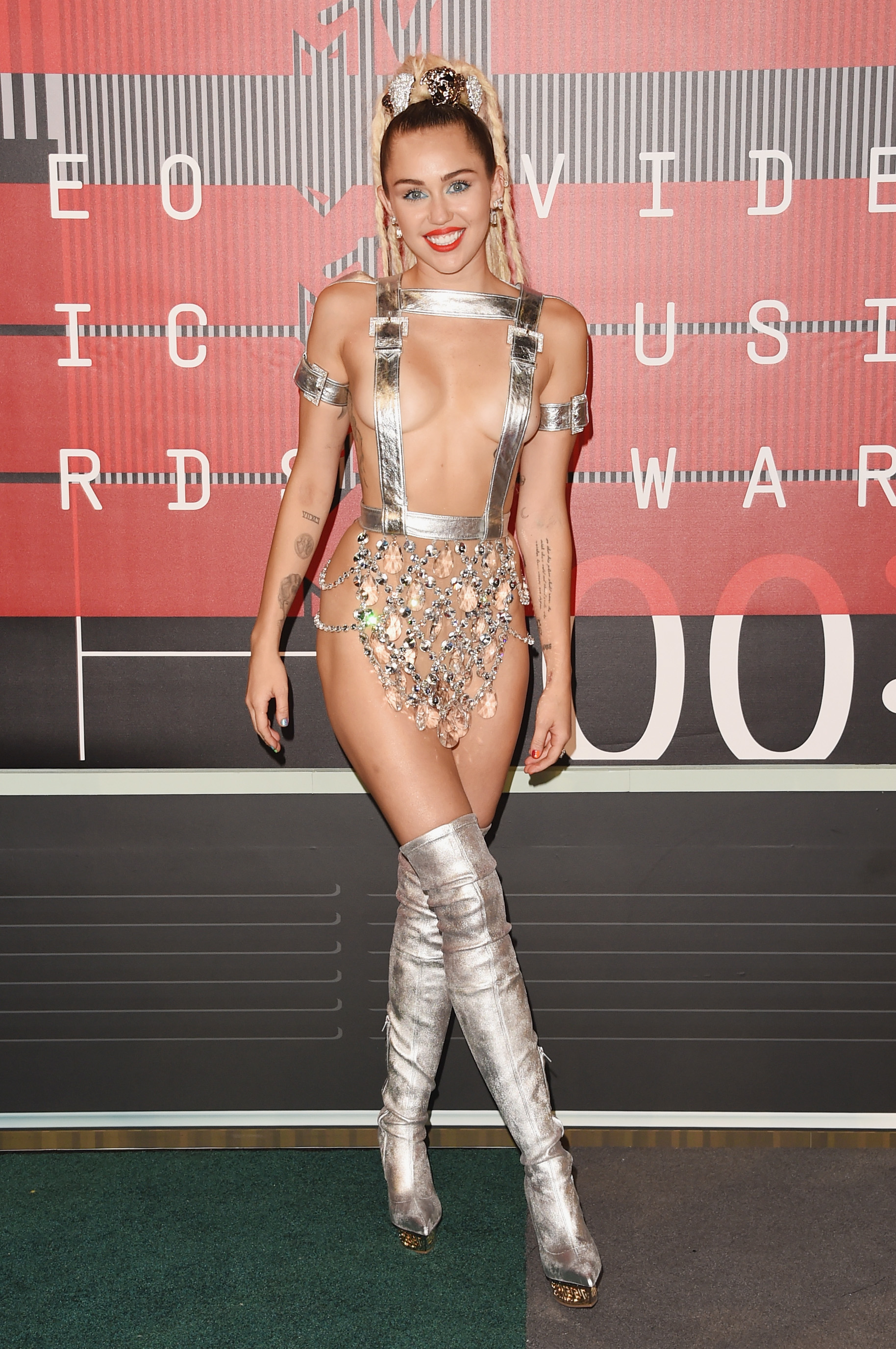 LOS ANGELES, CA - AUGUST 30:  Host Miley Cyrus, styled by Simone Harouche, wearing a custom Versace outfit and boots, attends the 2015 MTV Video Music Awards at Microsoft Theater on August 30, 2015 in Los Angeles, California.  (Photo by Jason Merritt/Getty Images)