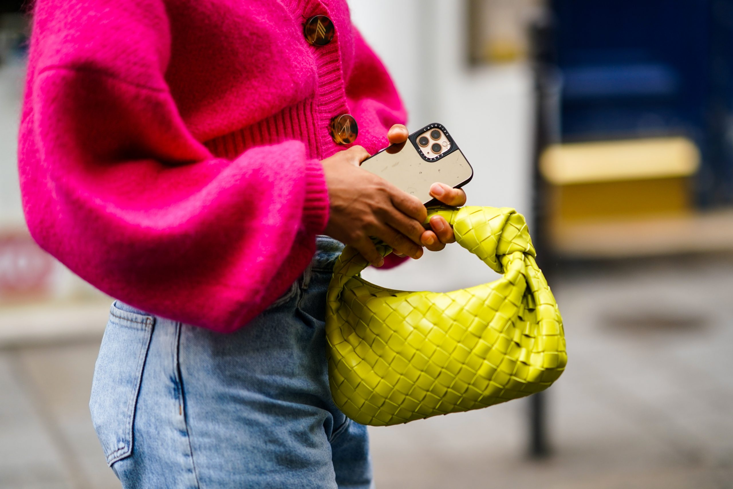 PARIS, FRANCE - OCTOBER 04: Ellie Delphine wears a neon pink wool cropped cardigan, blue denim ripped jeans, a yellow woven leather Bottega Veneta bag, outside Paco Rabanne, during Paris Fashion Week - Womenswear Spring Summer 2021, on October 04, 2020 in Paris, France. (Photo by Edward Berthelot/Getty Images)
